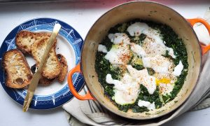 orange pot with green shakshuka in it and a plate with toast and a butter knife