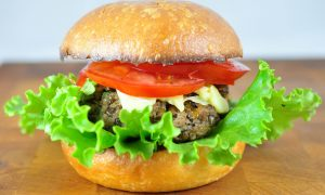 half veggie burger with a beautiful fluffy lettuce and tomato on top