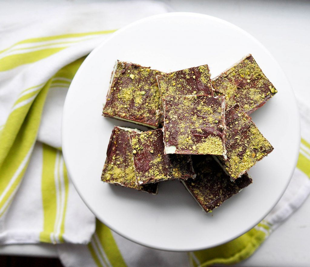 pistachio nanaimo bars from above on a white plate with a bright green striped tea towel
