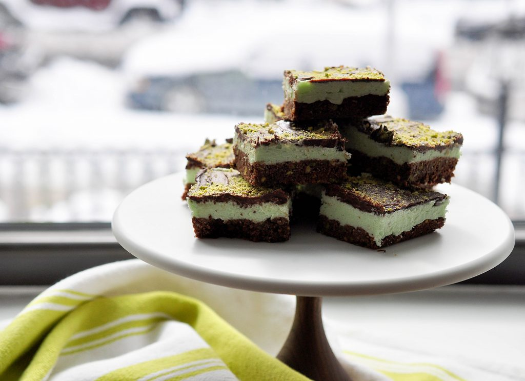pistachio nanaimo bars piled on a cake platter by a window