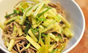 white bowl with Asian Noodle salad of soba noodles, cucumber shreds, basil and tomato