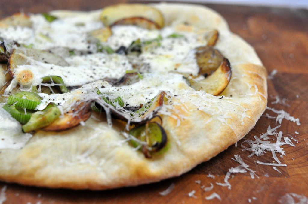side view of potato and leek pizza on a wooden board