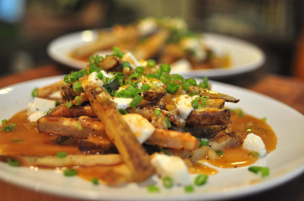 poutine! oven baked fries smothered in gravy, mozzarella and scallions on a white plate