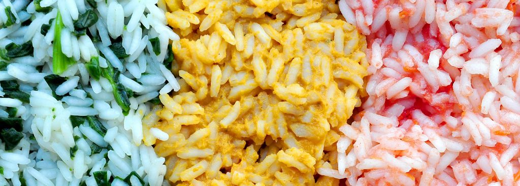 close up of rice with with green yellow and red vegetable mixed into it.