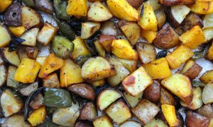 an expanse of roasted vegetables including potatoes, swee potatoes, peppers and squash