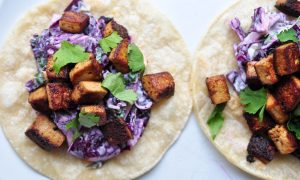 two tofu and peanut cabbage slaw tacos on a white background