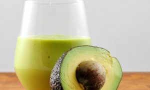 avocado milkshake in glass with half an avocado leaning on it