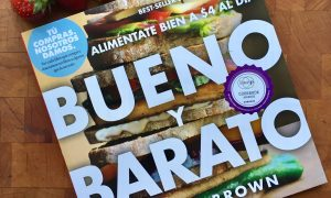 copy of Bueno Y Barato book with strawberries on a wood block background